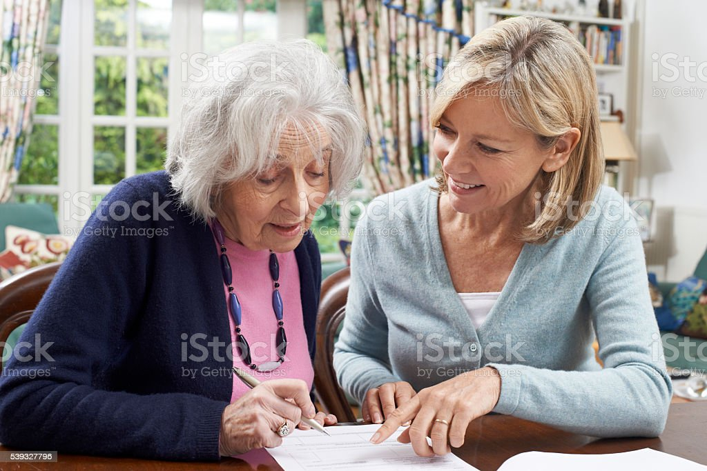Female Neighbor Helping Senior Woman To Complete Form stock photo