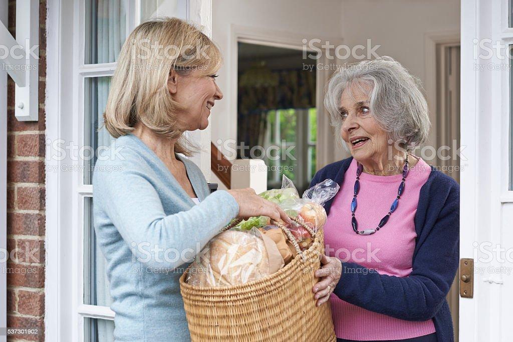 Female Neighbor Helping Senior Woman With Shopping stock photo