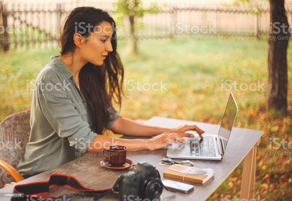Female novelist writing on the laptop stock photo