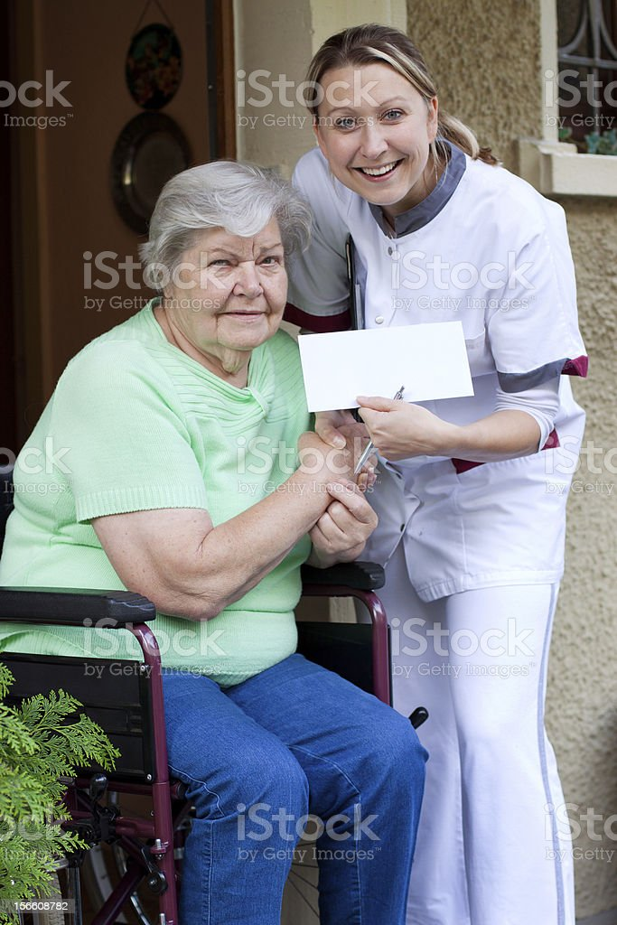 female Nurse and patient in a wheelchair royalty-free stock photo