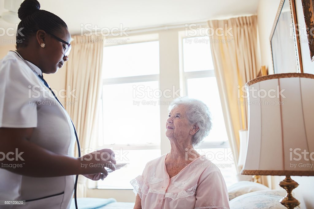 Female nurse assists an elderly female patient with medicines stock photo
