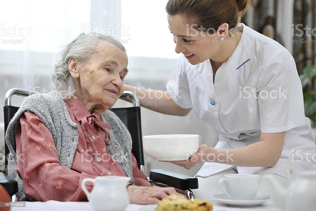 Female nurse bringing food to senior woman in a nursing home royalty-free stock photo