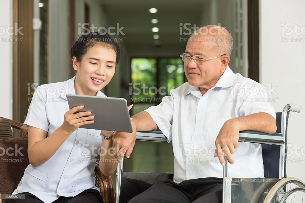Female nurse discussing over digital tablet with senior man stock photo