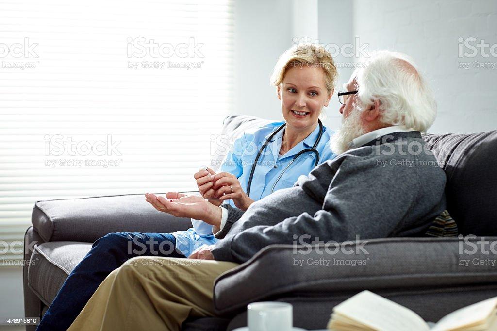 Female nurse giving medicine to elderly patient stock photo