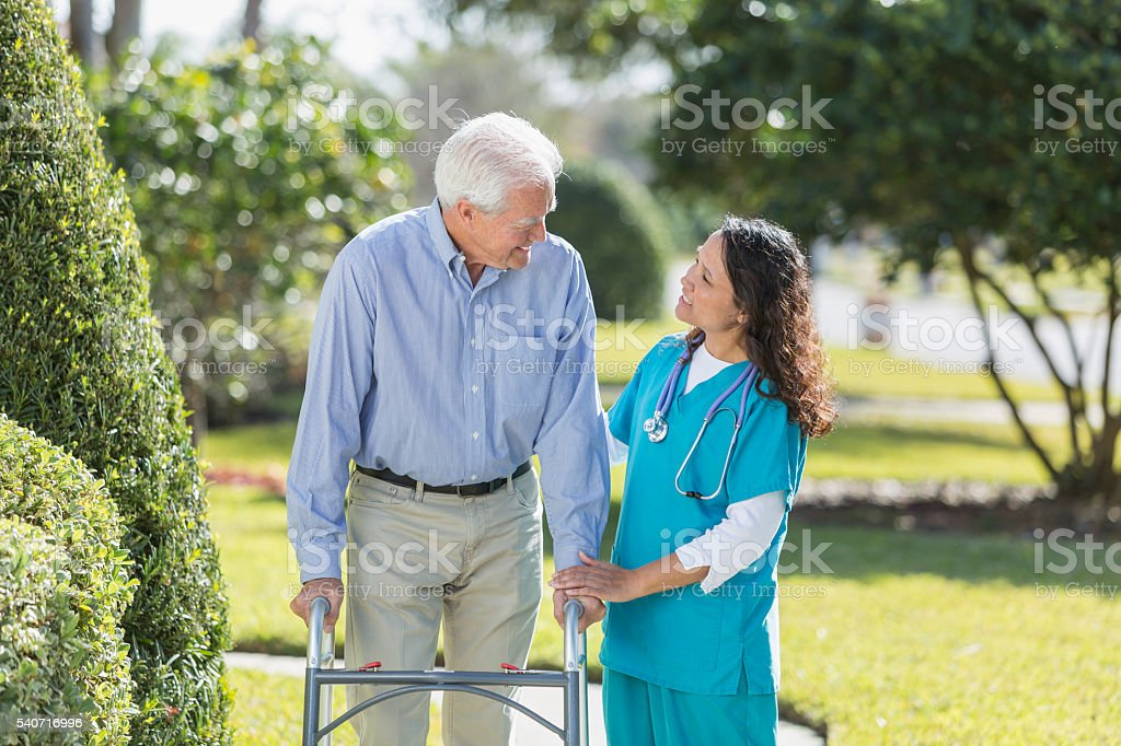 Female nurse helping senior man using walker outdoors stock photo