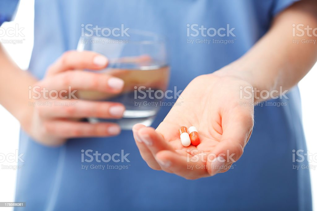 Female nurse holding two pills and a glass of water stock photo