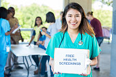 Female nurse holds 'Free Health Screenings' sign at health fair