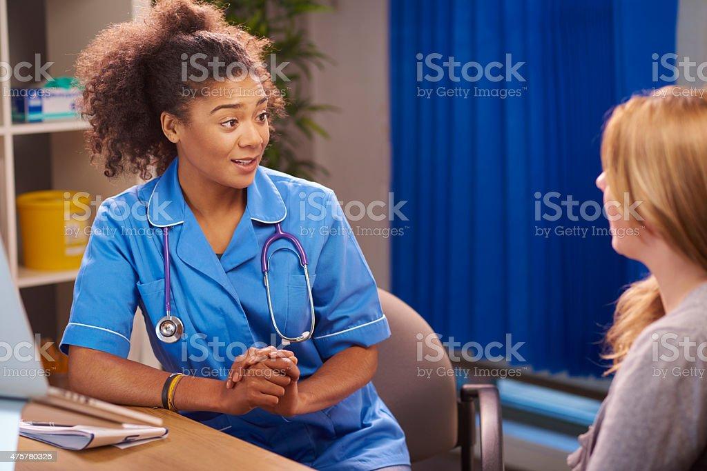 female nurse listening to patient stock photo