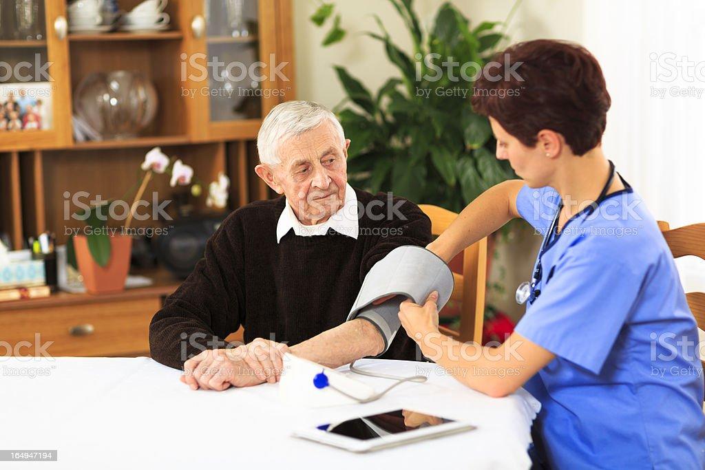 Female nurse measuring blood pressure of elderly patient stock photo
