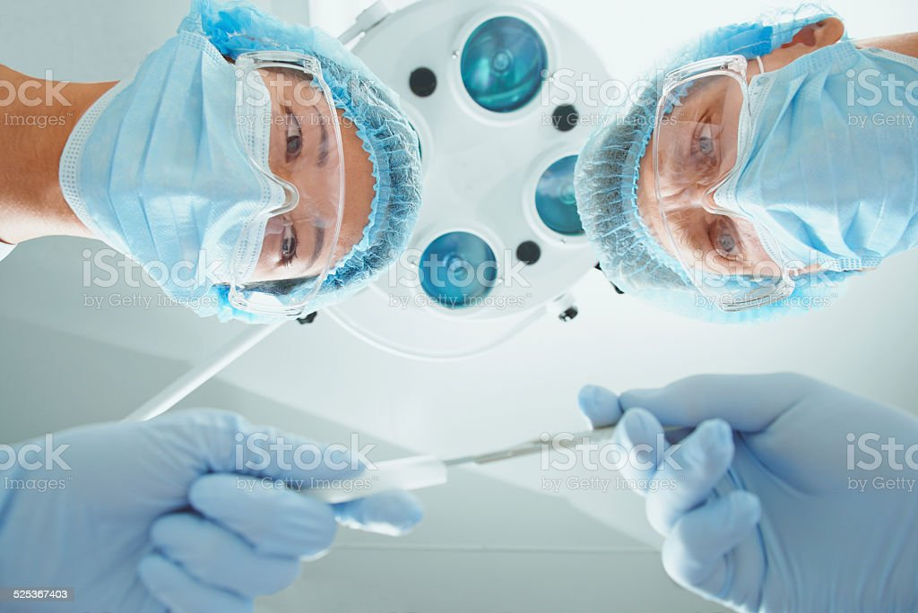 Female nurse passes a scalpel to surgeon stock photo