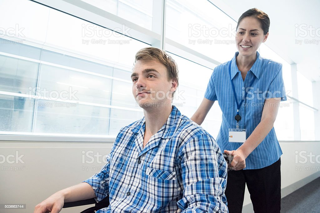 Female nurse pushing young man in wheelchair stock photo