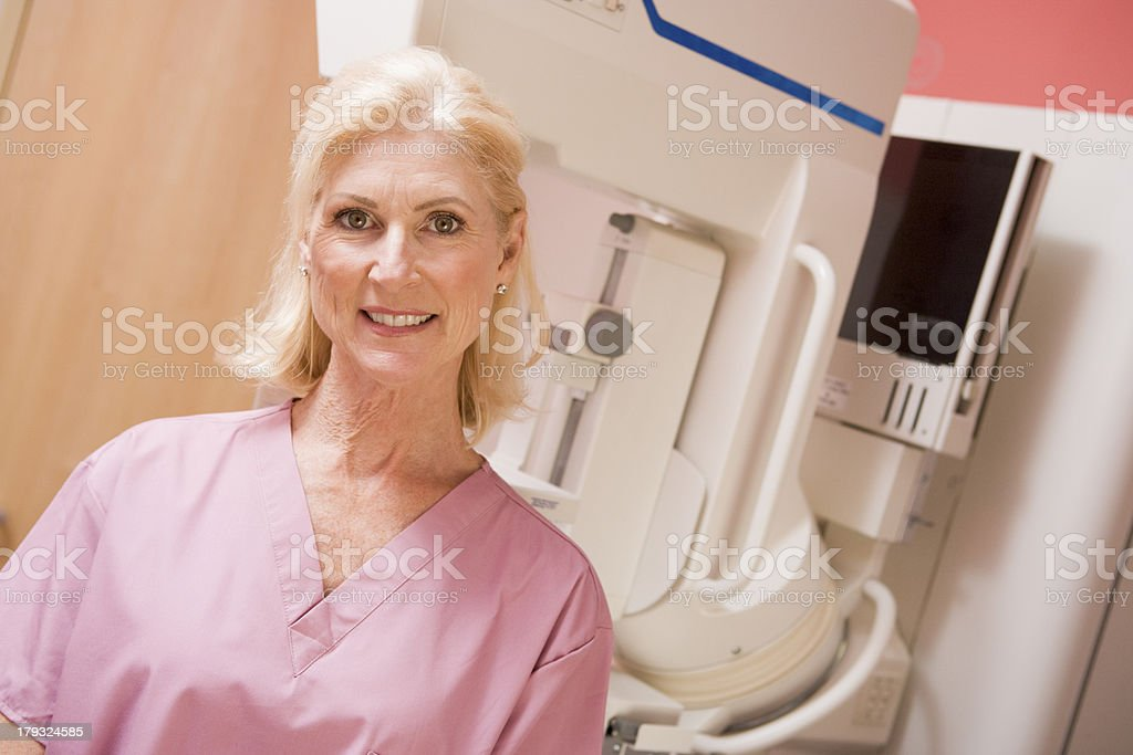Female nurse smiling with a mammogram machine royalty-free stock photo