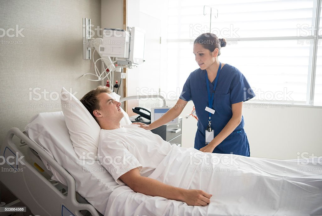 Female nurse tending to male patient in hospital bed stock photo
