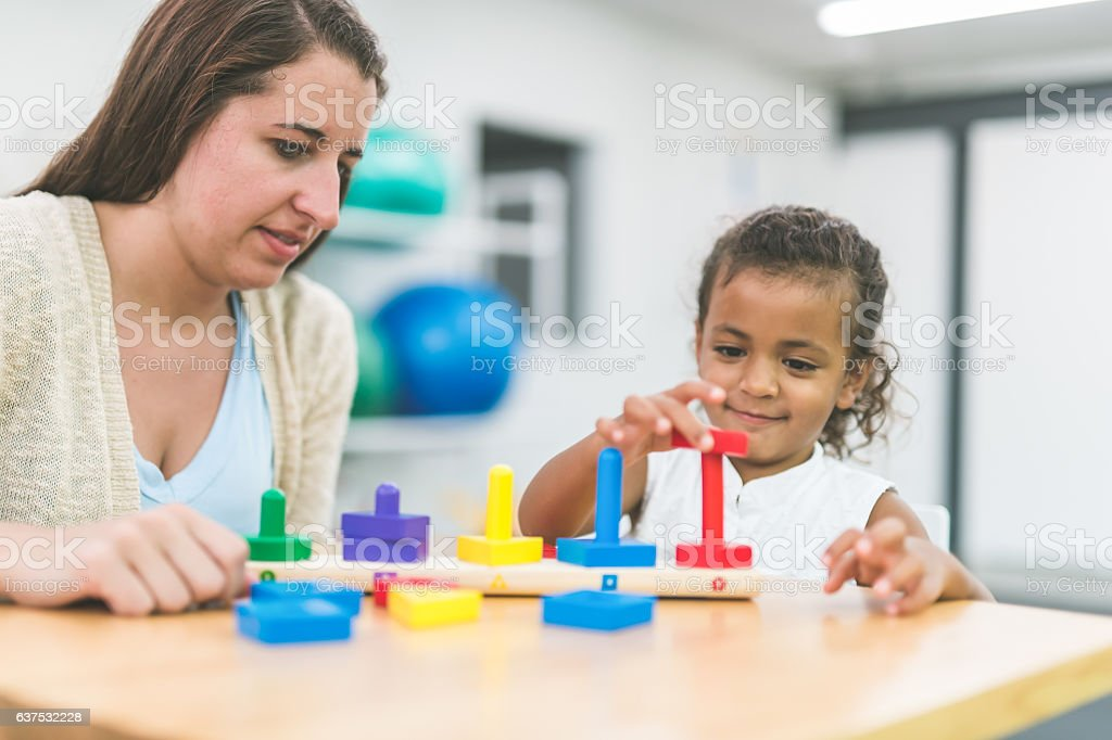 A female occupational therapist is doing rehabilitation with a child patient stock photo