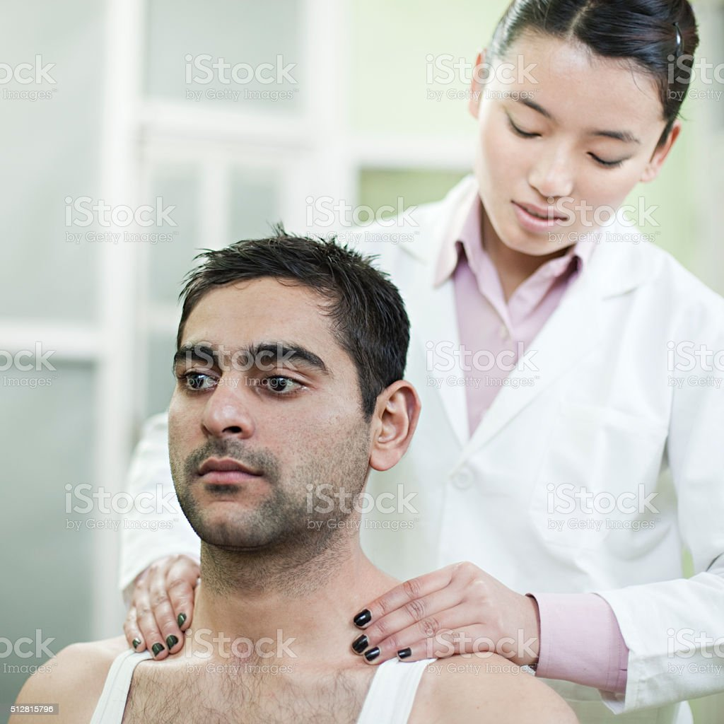 Female occupational therapist relieving Trapezius spasm of male patient. stock photo