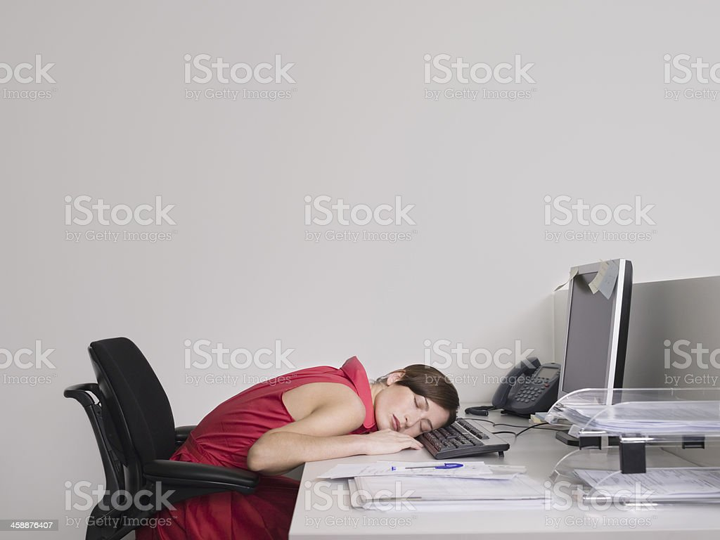 Female Office Worker Asleep At Desk stock photo