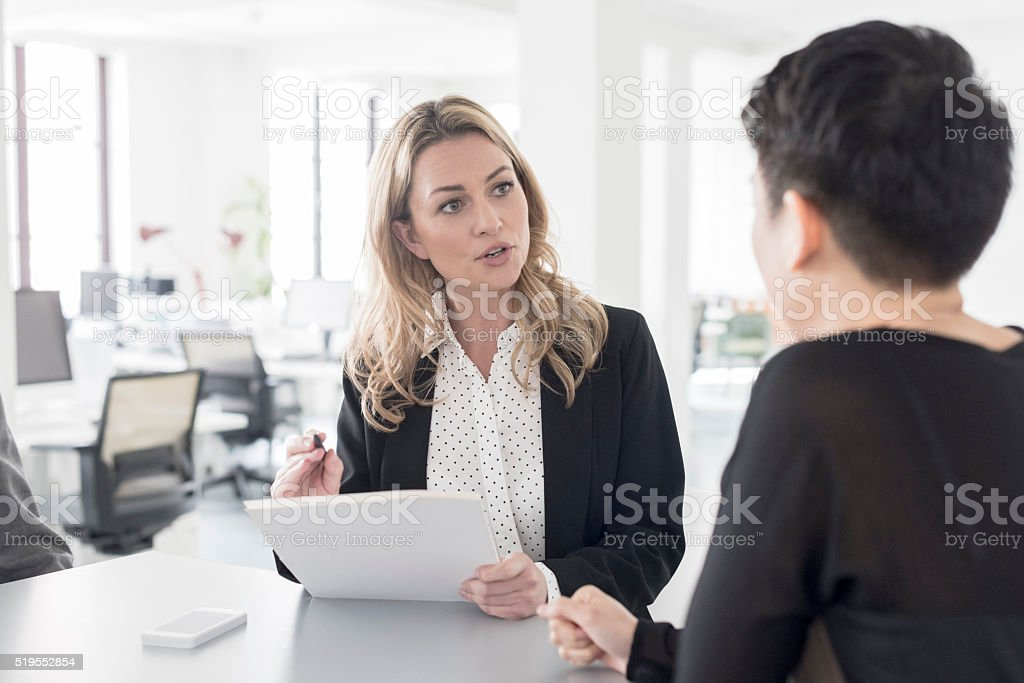 Female office worker discussing with colleague in modern office stock photo