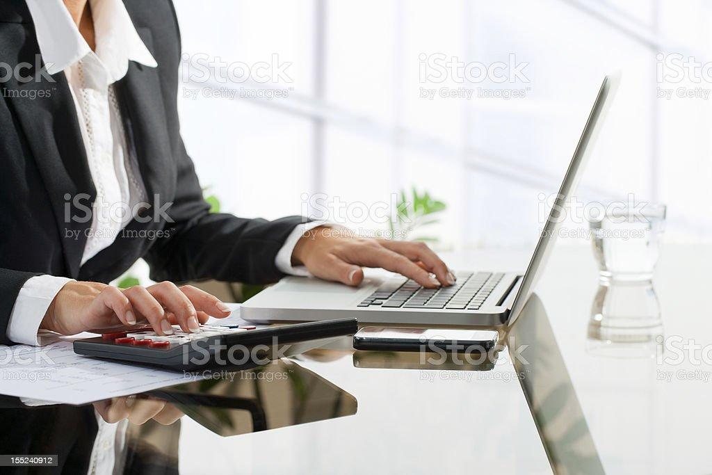 Employé de bureau, faire la comptabilité femme avec calculateur. photo libre de droits