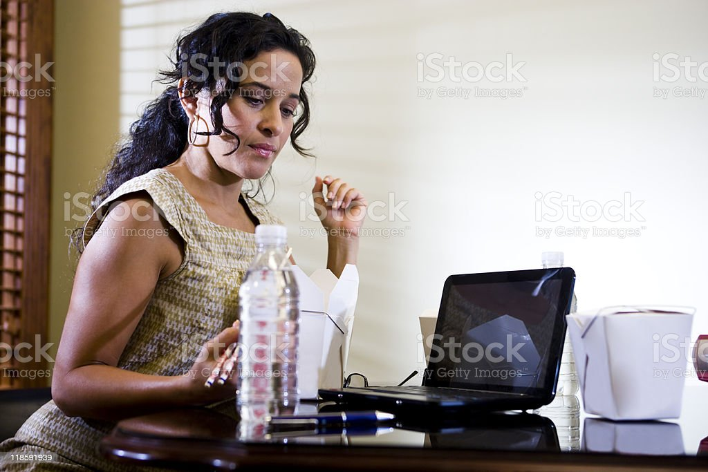 Female office worker eating take-out working on laptop royalty-free stock photo