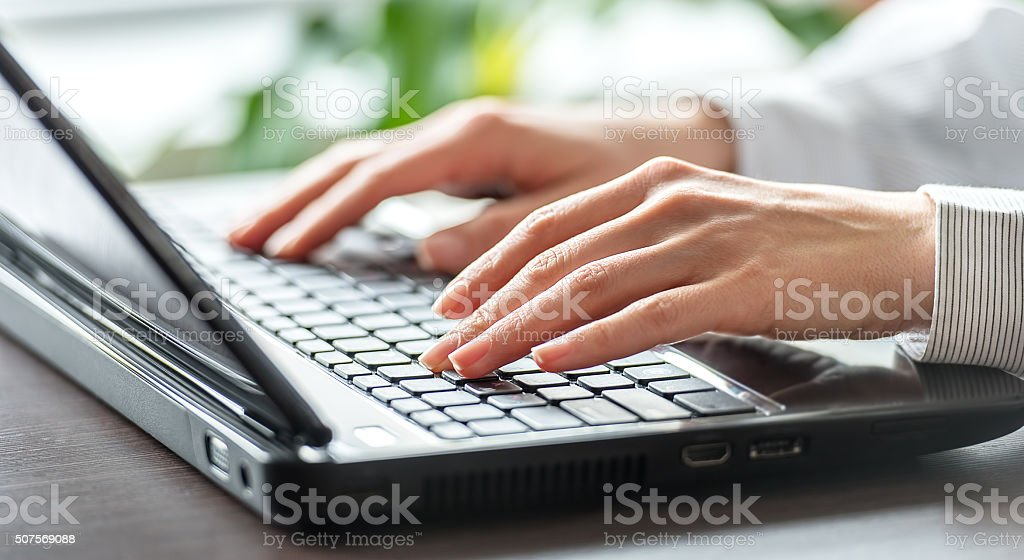 Female office worker typing on the keyboard. stock photo