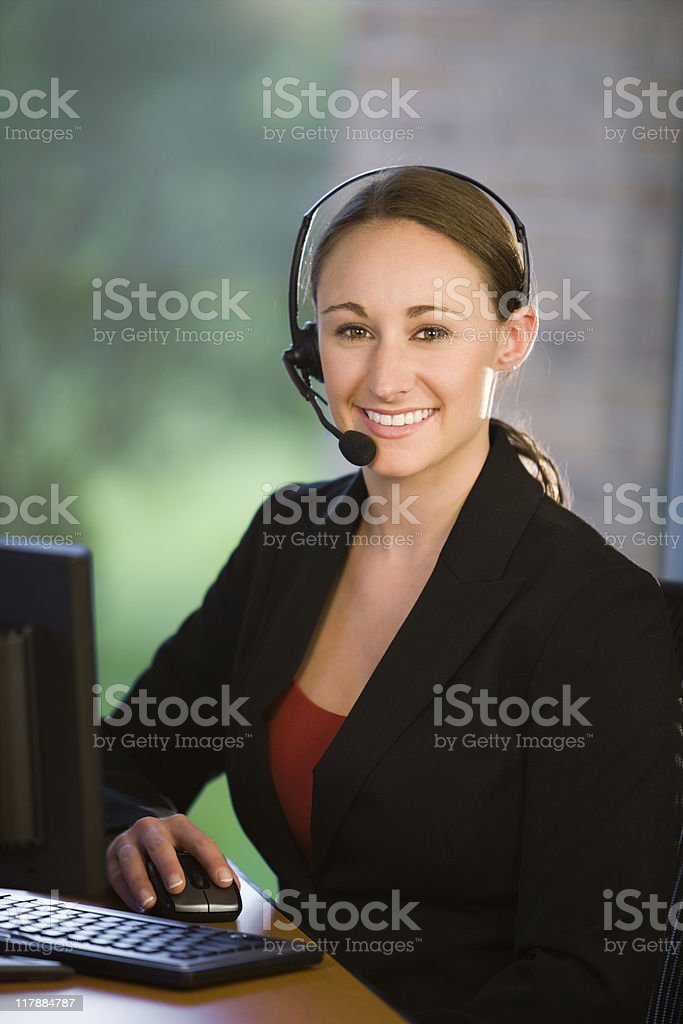 Female Office Worker Wearing Headset royalty-free stock photo