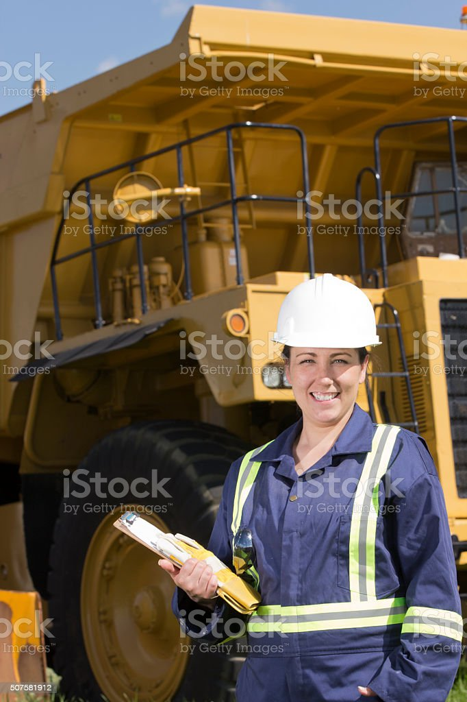 Female oil or construction worker in front of hauling truck stock photo