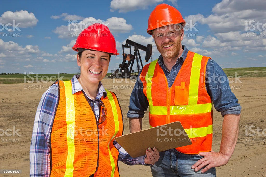 Female Oil Worker and Engineer at Pumpjack stock photo