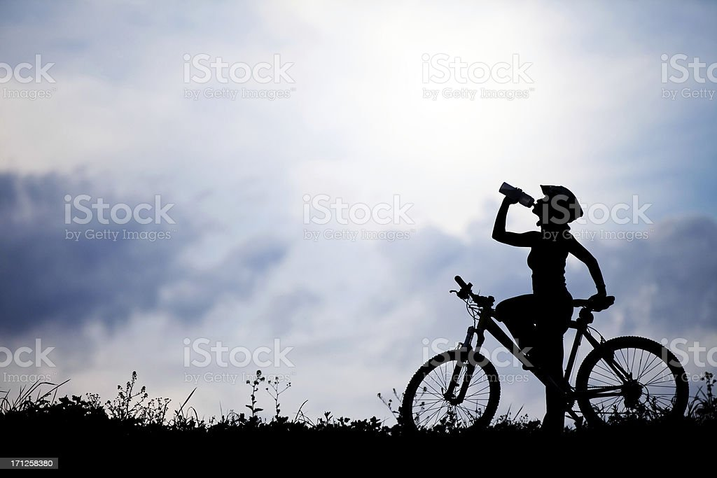 Female on a bicycle refreshing royalty-free stock photo