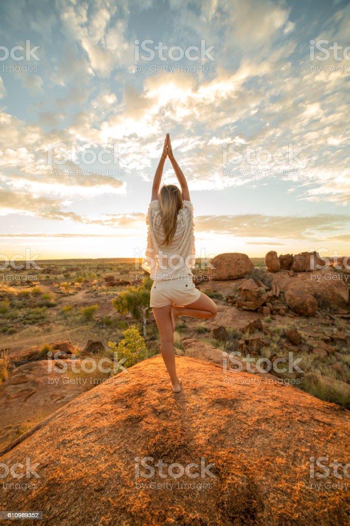Female on boulder exercises yoga at sunrise stock photo