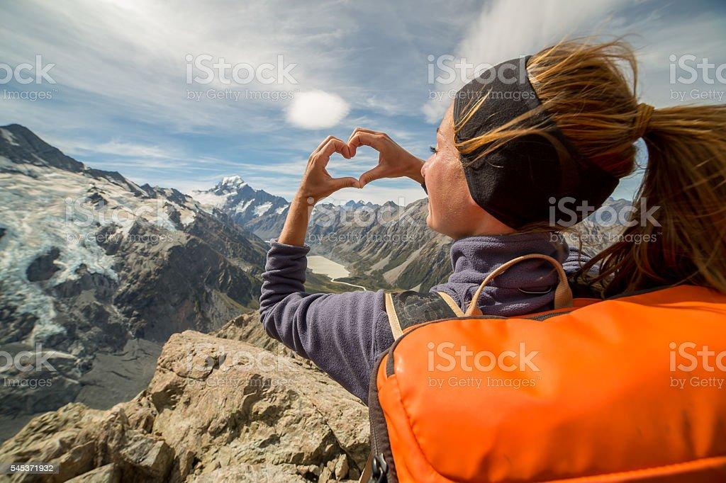 Female on mountain top makes heart frame towards Mount Cook stock photo