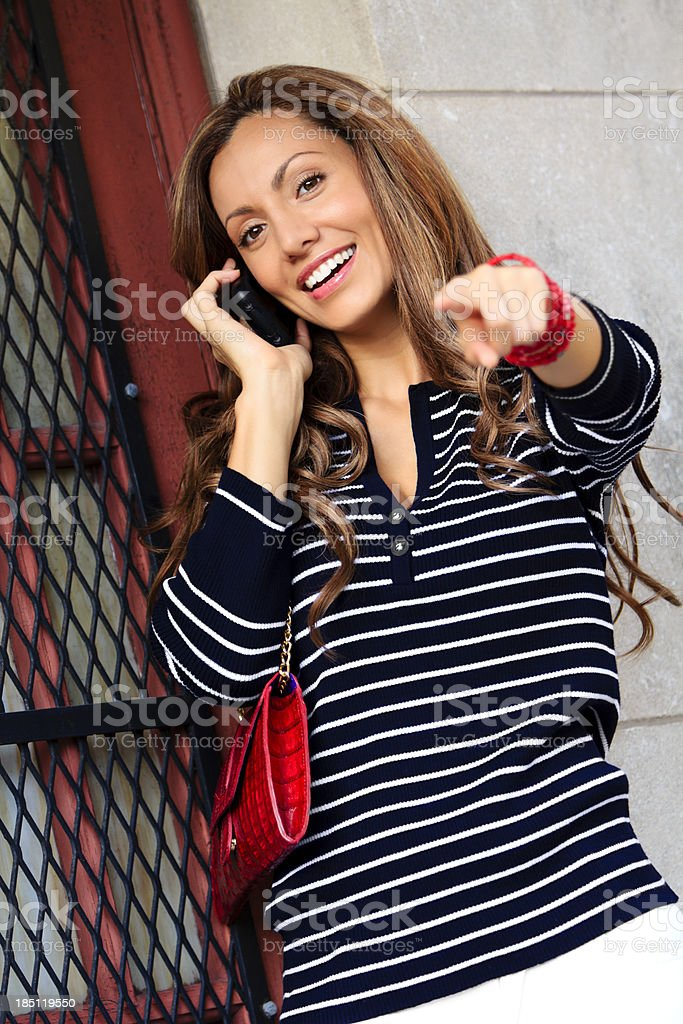 Female on phone pointing at camera stock photo