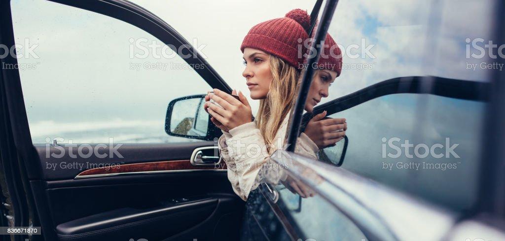 Female on road trip drinking coffee inside car stock photo