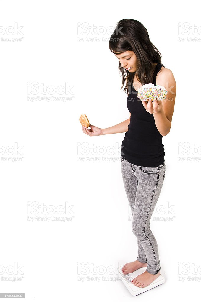female on scale eating junk food royalty-free stock photo