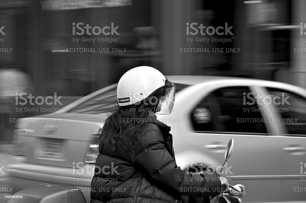Female on scooter passing by in SOHO, New York City stock photo