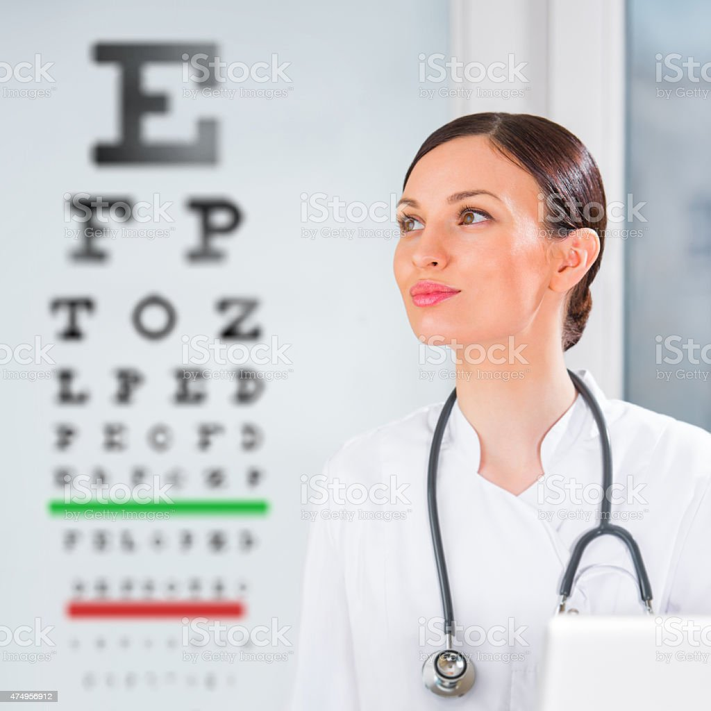 Female optician standing in front of eyesight test at hospital stock photo