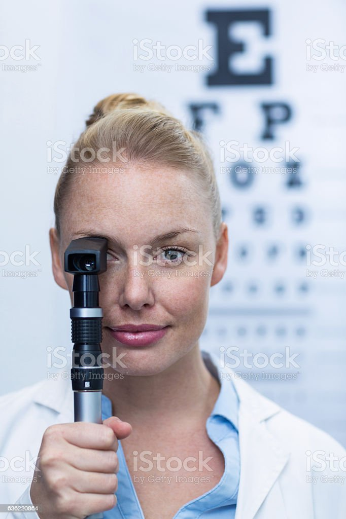 Female optometrist looking through ophthalmoscope stock photo