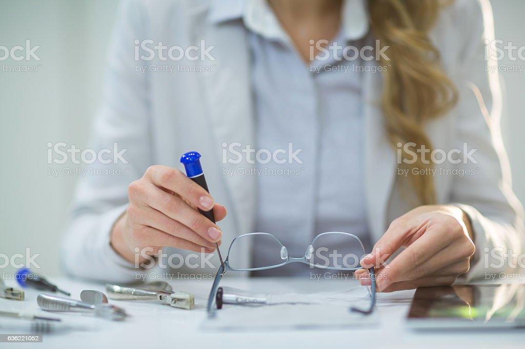 Female optometrist preparing glass frame stock photo
