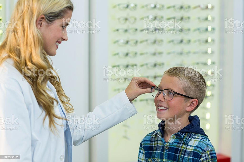Female optometrist prescribing spectacles to young patient stock photo