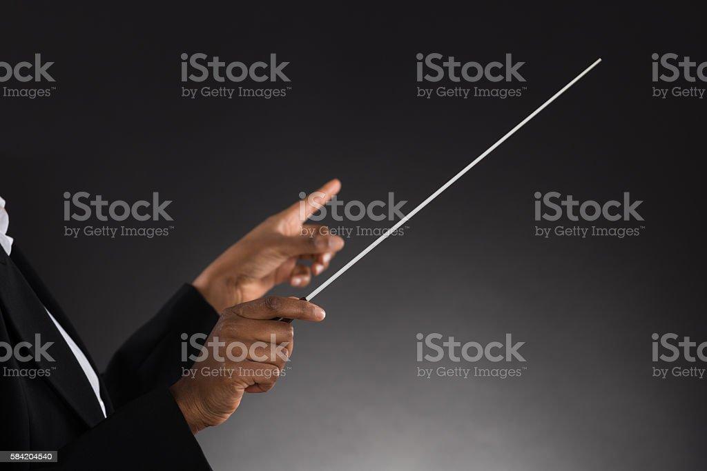 Female Orchestra Conductor Holding Baton stock photo