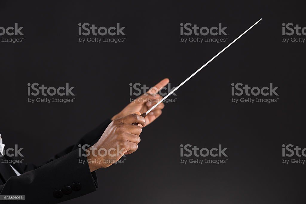 Female Orchestra Conductor Holding Baton stock photo