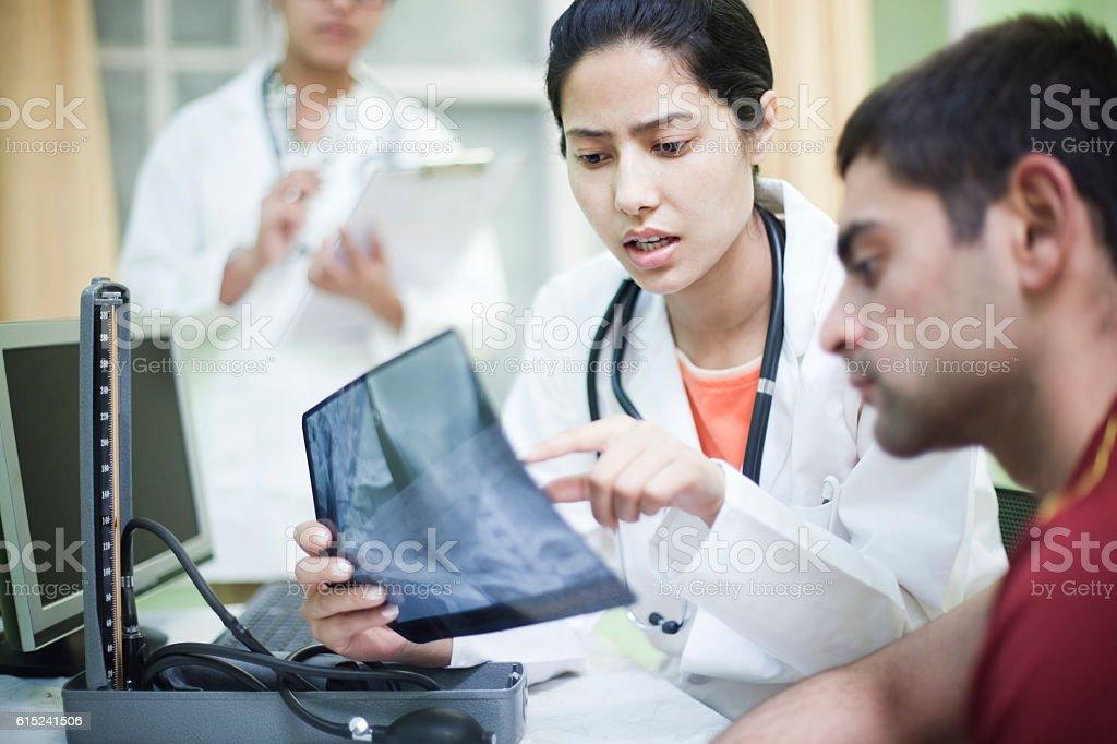Female orthopedics doctor examining x-ray of patient. stock photo