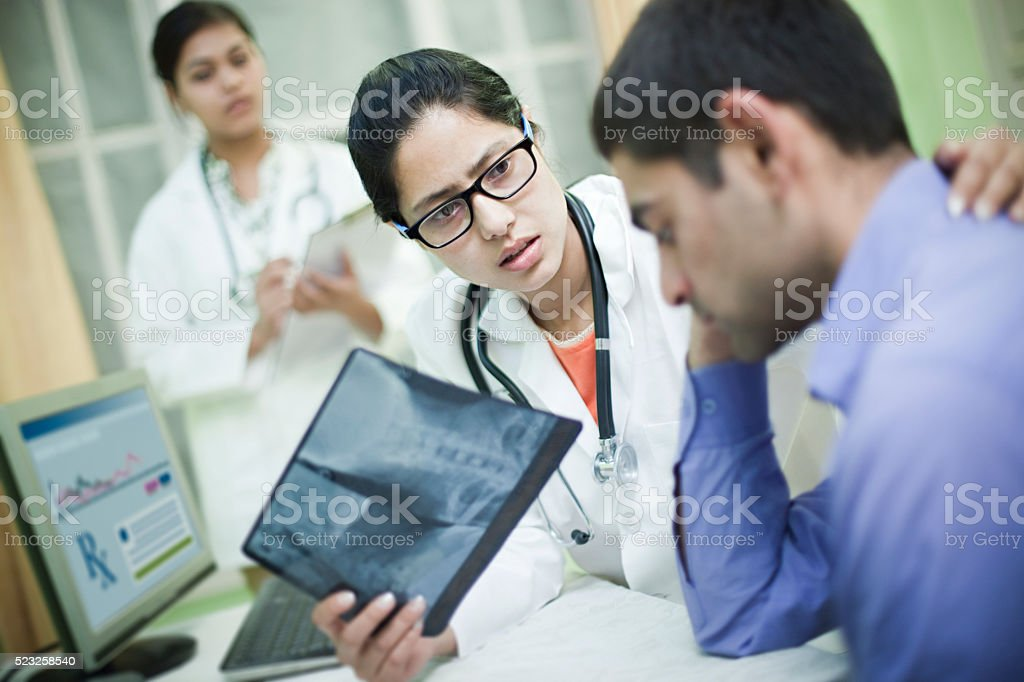 Female orthopedics doctor holding x-ray image and consoling to patient. stock photo