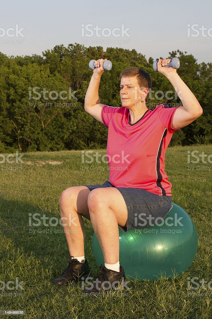 Female outside on a stability-ball perfoms a dumbell shoulder press. stock photo