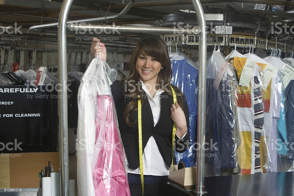 Female Owner Holding Clean Dress In Laundry stock photo