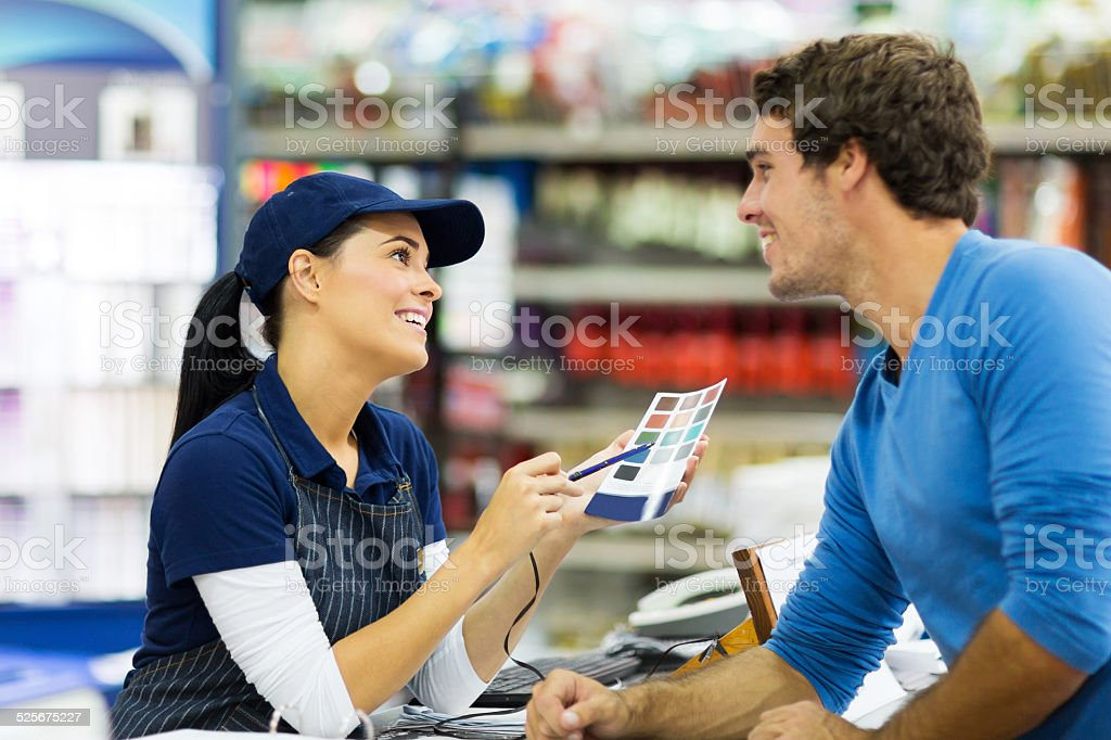 female paint store worker talking to customer stock photo