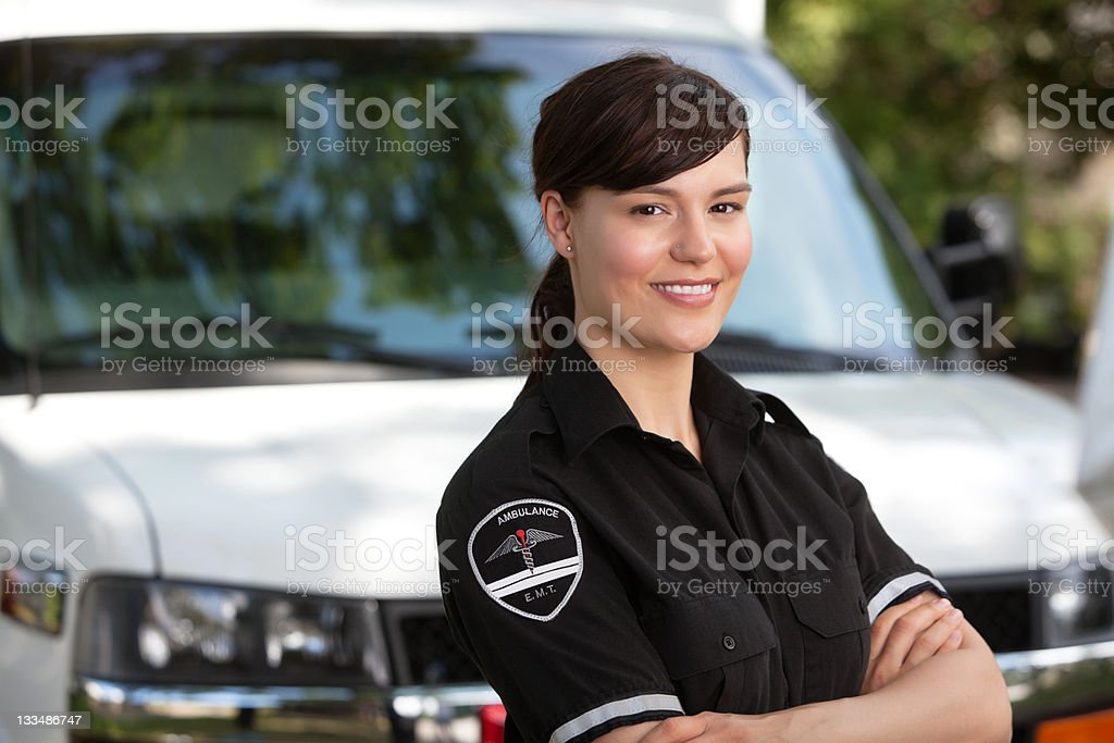 Female paramedic standing outside of her ambulance royalty-free stock photo