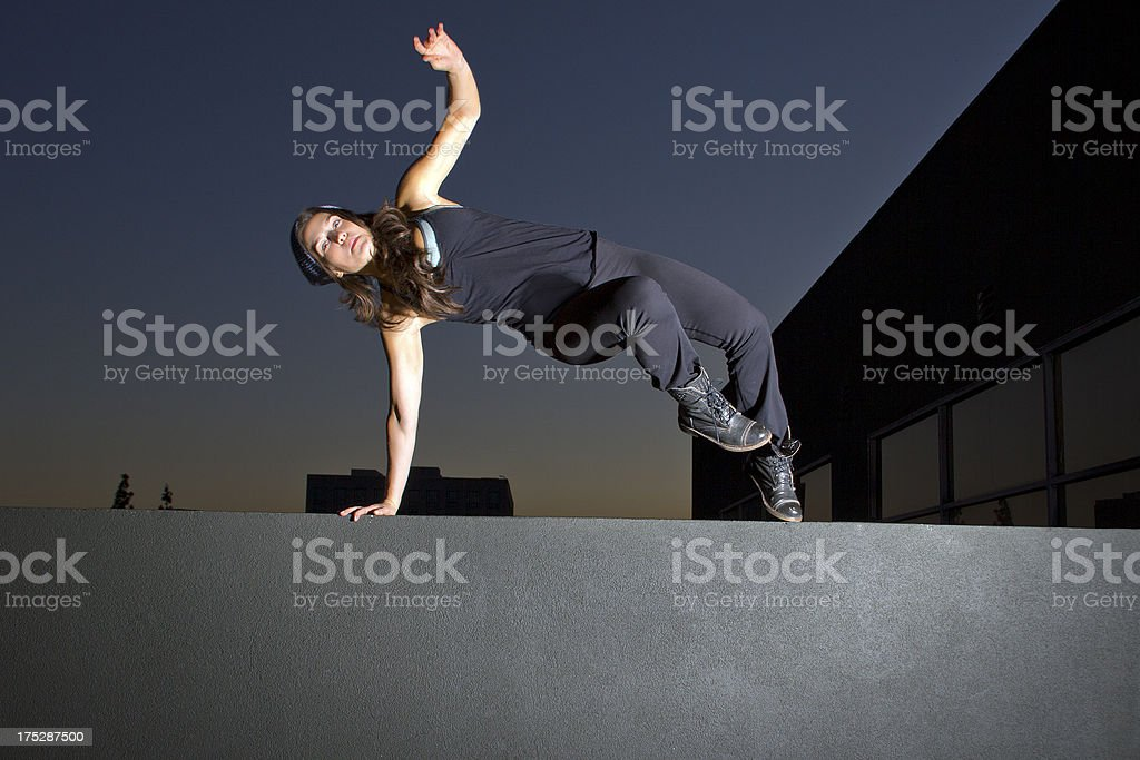Female Parkour Freerunner Jumping Off a Rooftop at Night royalty-free stock photo