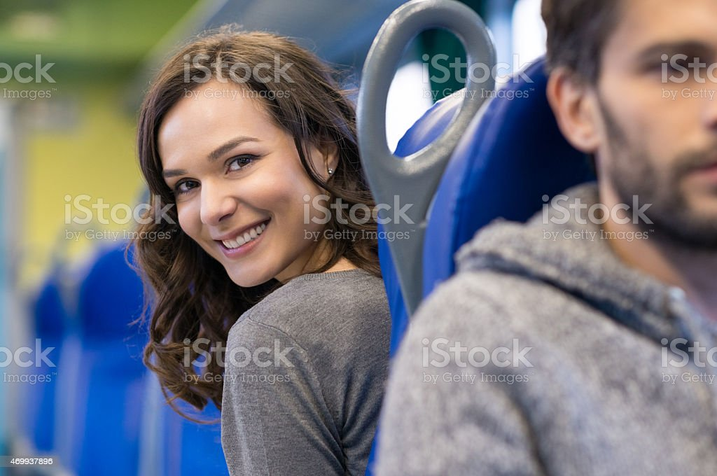 A female passenger in a train cabin looking back and smiling stock photo