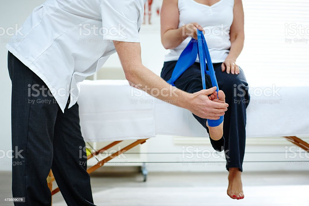 Female patient doing some special leg stretching exercises stock photo