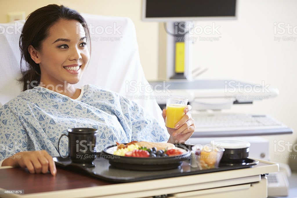Female Patient Enjoying Meal In Hospital Bed stock photo